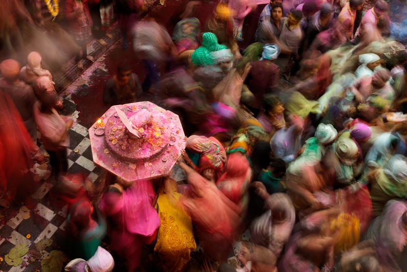 Vrindavan, India. A pedestal holds a small metal sculpture of a cow and calf, which are sacred for Hindus. In this extended exposure, Holi celebrants are paying respect and touching the pedestal for a blessing.
