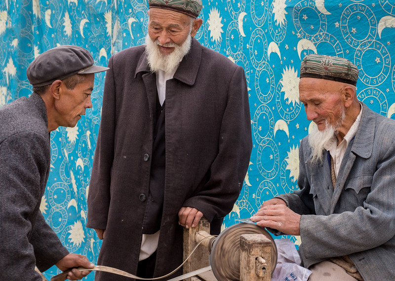 Kashgar, China. On the Muslim Kurban holiday, each devout Muslim family sacrifices a sheep, and a sharp knife is important to that mission. A customer, on the left, provides power to the grinding wheel as a knife is sharpened.