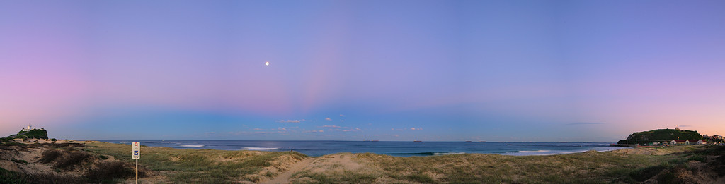 Nobbys Beach Sunset - It was a beautiful sunset at Nobbys. As the sun went down behind me, the hill of Newcastle started casting its shadow while still leaving the beautiful pastel pinks in the sky surrounding the moon.