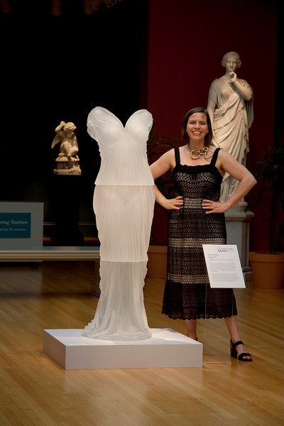 Karen LaMonte standing with her sculpture Undine, a cast glass dress, in the neoclassical gallery of the Chrysler Museum