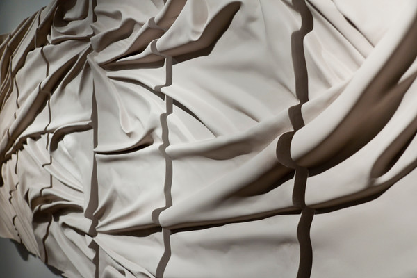 Detail of monumental drapery sculpture Vortex in ceramic, mounted on wall