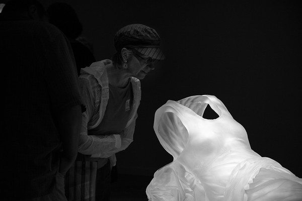 Art lover looking inside a sculpture of a dress at the impression of an absent female body, by Karen LaMonte