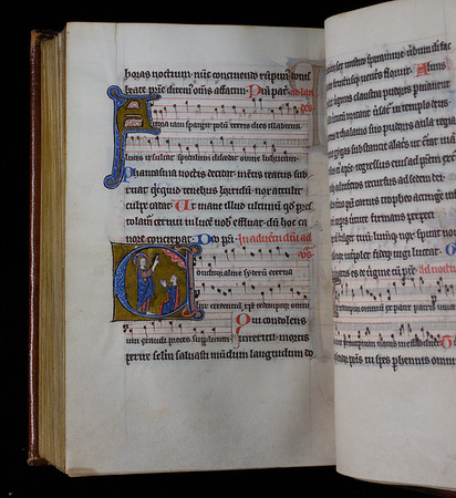 This small, beautifully written and richly decorated liturgical psalter from the fifteenth century must have been intended for individual use. The forms of the hymn melodies are not those of the Use of Sarum, but of those found in Benedictine chant books. It has been speculated that the volume could have come from Worcester. Queens' MS 29 gives the texts of the psalms, canticles and regular hymns sung week by week at the Divine Office (eight services each day), together with the Litany of Office of the Dead. A hymnal is appended with texts and melodies of hymns for the seasons and feasts of the year. <br><br> This opening shows Advent hymns with an illuminated initial C depicting Christ (left) blessing a kneeling figure on the right under a red cloud with white stars. <br><br> <b>Title:</b><i> Psalter </i> (15th century) <br> <b>Shelfmark:</b> Queens' College MS 29<br> <b>Provenance:</b> Gift of John Cabourne on his matriculation to the College in 1632
