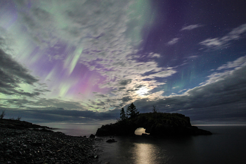 "SATURDAY, JUNE 1, 2013<br /> <br /> AURORA 3821<br /> <br /> ""Hollow Rock Dreamscape""<br /> <br /> Last night before going to bed, I looked at the spaceweather.com website just in case there were any reports of aurora activity. As luck would have it, an interplanetary shock wave had just arrived and was sparking aurora activity. The source of the shock wave was unknown, but researchers say it could have originated in a transition zone between high and low speed solar wind streams. The shock wave ended up generating nearly 15 hours of geomagnetic storming.  I left the house at 11:30 PM and spent the next 4 hours searching for openings in the clouds so I could photograph the lights. <br /> <br /> It looked like the sky might be clearing to the northwest so I decided to head in that direction. I drove up the Arrowhead Trail and found a nice shooting location near Irish Creek. The clouds were breaking up just enough to let the aurora shine through, and it was magnificent! Light fog along the ground added an extra bit of mystery to the scene and all around me the spring peeper frogs were singing as the lights danced overhead. I also heard a couple of barred owls talking to each other in the distance!<br /> <br /> I continued driving up the trail until I arrived at McFarland Lake.  In my opinion, McFarland is one of the best places in Cook County to watch the northern lights.  Unfortunately when I arrived at the lake the sky was still completely covered with clouds. I hung around here for almost two hours hoping the sky would clear, but it never did. Several times, however, the cloud cover got thin enough that the glow from the lights could be seen through the clouds. <br /> <br /> As I drove back down the Arrowhead Trail the sky was completely socked in with clouds and thick fog covered the ground.  When I got back to Highway 61, however, the fog had lifted and there were some openings in the clouds. By the time I was driving by Hollow Rock Resort on the Lake Superior shoreline the clouds were receding quickly and the sky was full of dancing northern lights. Of course I had to stop at Hollow Rock once I saw these conditions!  Since the view here is more east/southeast than north, opportunities to see the aurora over the rock are rare.  This photo was made about 3:30 in the morning and was the last shot I made before heading home and crawling into bed. It sure was a fantastic night! <br /> <br /> Camera: Canon EOS 5D Mark II<br /> Lens: Canon EF 17-40mm<br /> Focal length: 17mm<br /> Shutter speed: 20 seconds<br /> Aperture: f4.0<br /> ISO: 1000"