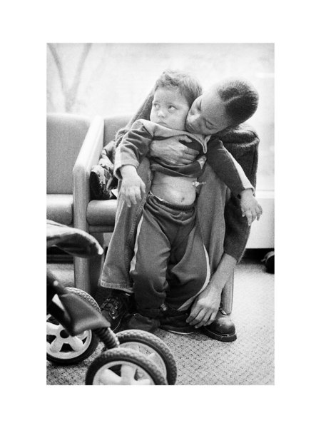 While in a waiting room at Johns Hopkins Hospital, Jeanette helps Max take to his feet. Weight bearing exercises are necessary to build and maintain strength in his legs and hips. We use activities such as assisted standing in an attempt to encourage normal bone and muscle development, as well as to stimulate his own ability to stand unassisted.