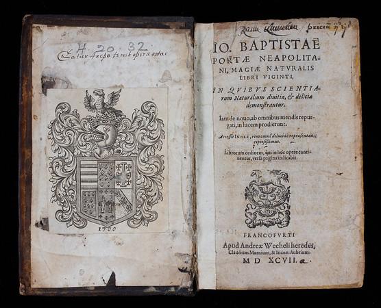 "Five-word 2D Latin palindrome, also part of the Rotas-Sator square in a 17th century hand above armorial bookplate of Queens' College: 'Sator arepo tenet opera rotas' <br><br> <b>Author:</b> Giambattista della Porta<br> <b>Title:</b><i> Magiae naturalis </i> [Natural magic] (Frankfurt, 1597) <br> <b>Shelfmark:</b> H.20.32  <a href=""http://idiscover.lib.cam.ac.uk/permalink/f/1nnjft8/44CAM_ALMA21392239250003606""> (catalogue record)</a>"