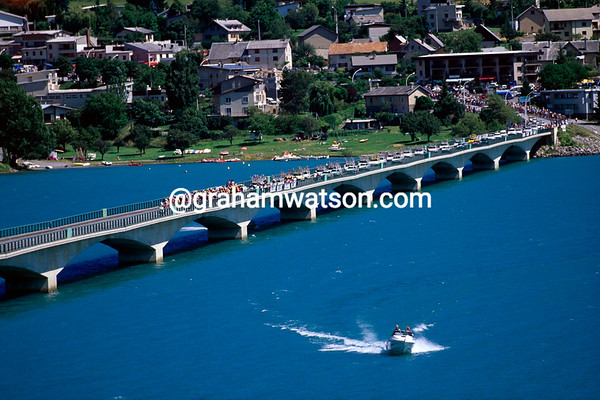 The Spectacle - the 1996 Tour peloton crosses the bridge over the Serre-Ponçon reservoir in the Alps.
