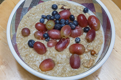 Steel cut oatmeal with grapes, blueberries, nuts; great breakfast food.