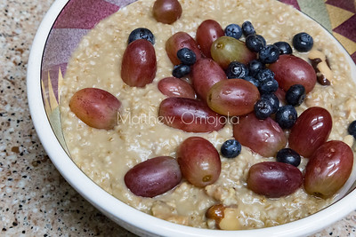 Oatmeal with nuts, blueberries and grapes. Great breakfast food.