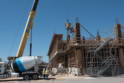 Construction crew pours concrete mix into the second floor column of Tidal Hall.
