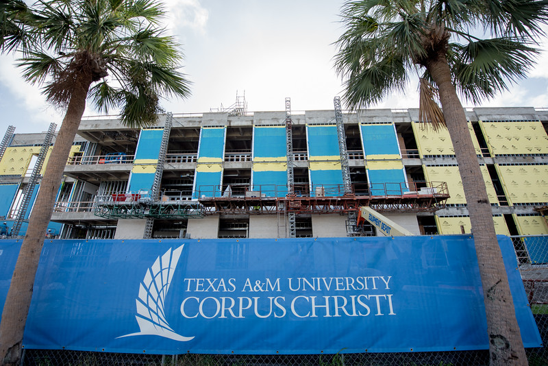 Construction crews place brick on the exterior walls on the east wall of the Tidal Hall building.