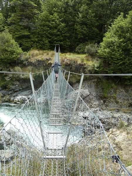 Janis crosses the swingbridge heading to Kiwiburn Hut on New Year's Eve.