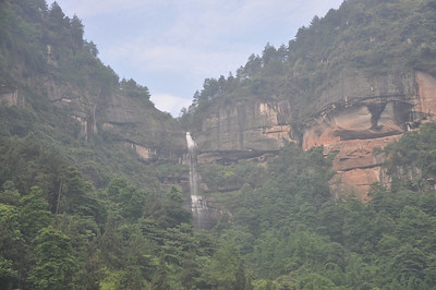 "Another shot of the waterfall...the tracksite is obvious now in this photo, yet I still didn't see it in the thick sandstone layer...!  At about this point, our vehicles were forced to a stop by road repair at a point where a recent little flood had streamed off a hillside and carved away part of the road on its way into the valley.  So I was told we'd have to get out and walk for about an hour, hour-and-a-half or so.  I thought that meant ""following the road.""  Silly me!  The road ended maybe a few more hundred yards up anyway...and then we turned off..."