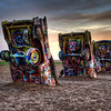 "This is from the famous Cadillac Ranch in  Amarillo, Texas. Some want to believe that an eccentric Texas millionaire (and those do exist!) would buy one Cadillac after another and when it was time to buy a new one, he would have the old one buried nose first on his land..... However, the truth is, the Cadillac Ranch was a planned artistic endeavor; as a tribute to America's best automobile, a collective of artists called Ant Farm decided to place 10 Cadillacs, ranging from a 1949 Club Coupe to a 1963 Sedan, in a wheat field located west of Amarillo. And the millionaire Mr. Stanley Marsh 3, a local helium tycoon, provided some place for the cars to rest. Ten big holes were dug and the cars were driven with their front end into them. But, some of the old story is true:  Texas millionaire <a href=""http://en.wikipedia.org/wiki/Stanley_Marsh_3"" target=""_blank"">Stanley Marsh, 3 </a>IS rather eccentric. He is also said to be very down to earth, quickly disregarding the ""III"" as too pretentious and using ""3"" instead. And in 1973, he invited a San Francisco artists' collective called the Ant Farm to help him in the creation of a unique work of art for his sprawling ranch just west of Amarillo. Built along the tattered remains of historic <a href=""http://en.wikipedia.org/wiki/U.S._Route_66"" target=""_blank"">Route 66</a>, the cars were meant to represent the ""Golden Age"" of American automobiles. Most of the cars, model years from 1948 to 1963, were purchased from junk yards, and averaged about $200. </span></span></span> At first, the cars displayed their original paint jobs – turquoise, banana yellow, gold, and sky blue, but barely was the monument complete, when people were scratching or painting their names in the cars. Over time, vandals and souvenir hounds smashed the windows, made off with all the chrome, radios, speakers and even some of the doors. The wheels have since been welded to the axles to prevent more theft. However, Marsh still says ""We think it looks better every year.""....</span>  <span style=""font-size: 10pt;"">And it is rather nice that all visitors are allowed any time, day or night...."
