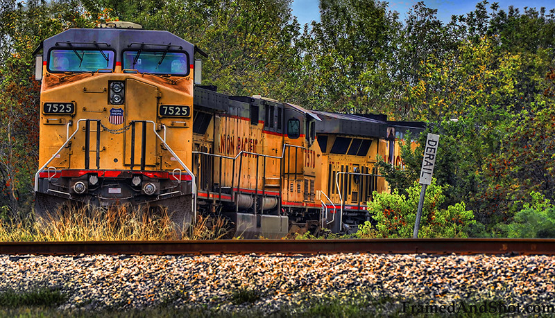 "Train Approaching<br /> Or actually not – This Union Pacific was parked on a sidetrack and did not approach us. It was standing perfectly still, in great contrast to the rails in front and the forest behind.  In a densely populated part of west Houston, Americas fourth largest city, and at one time a part of the wild west…<br /> Processed in Topaz adjust to enhance the ""grittiness"" of the train."