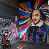 Street musician playing near a mural by James Cochran, on Clink Street near the new Old Globe Theatre, on the south bank of the Thames.  Photo by Jonathan.