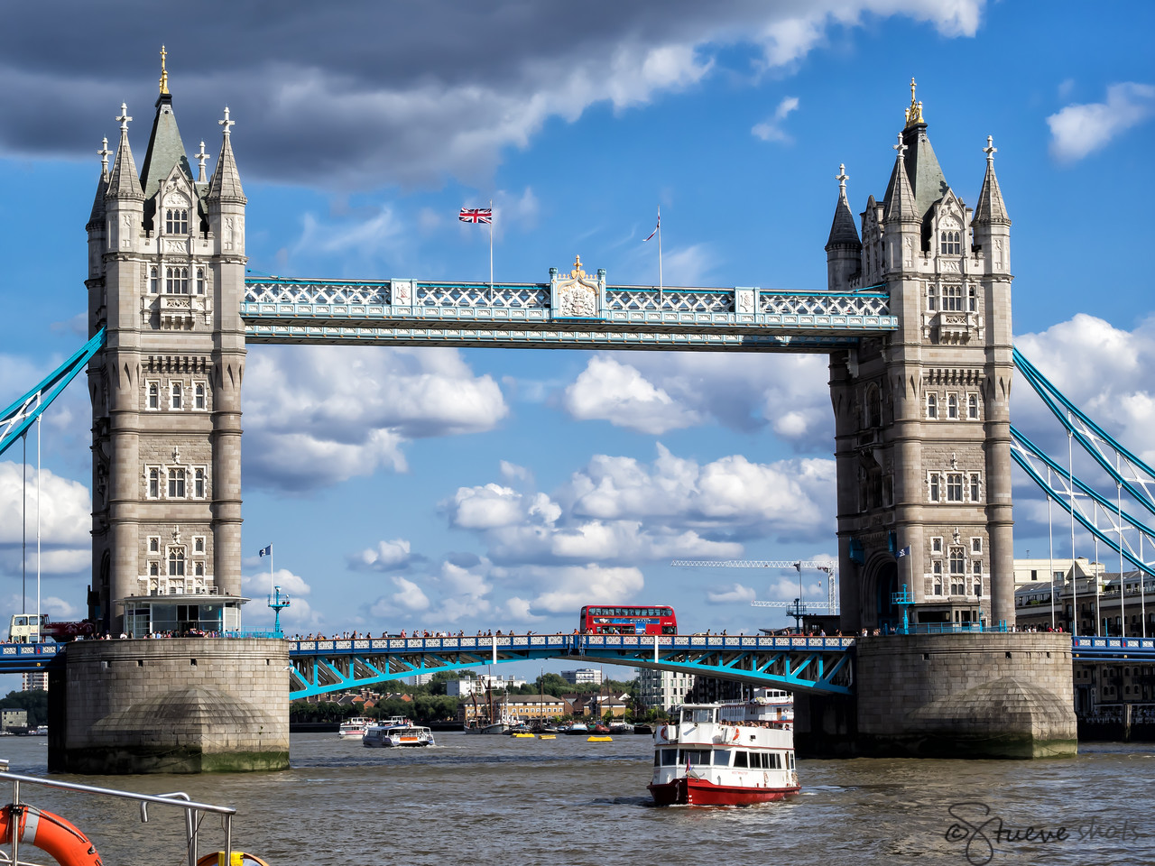 In Which the Union Jack Flies Full over the Tower Bridge Whilst a Double-Decker Bus Crosses the Thames.