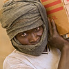 A WFP worker carrying a case of vegetable oil