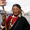 Tibetan pilgrim with a prayer wheel at Potala Palace in Lhasa, Tibet