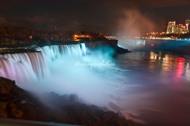 Niagara Falls at Night with both the American Falls and Horseshoe Falls illuminated. Across the water is the Canadian side of the falls.