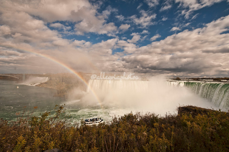 NIagara Falls. A rainbow arches over American Falls and Horseshoe Falls as the Maid of the Mist tour boat approaches.
