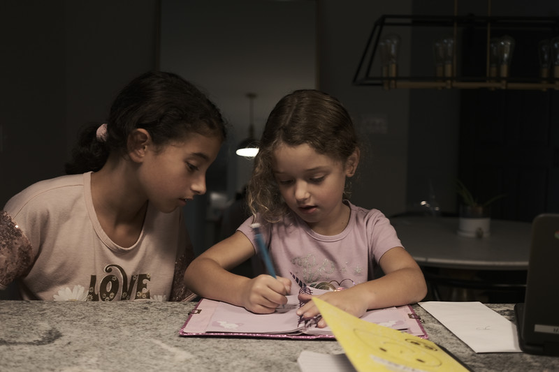 lyla helping willow with her letters - even though they can't go to school, doesn't mean they can't learn at daddy school - we did reading, writing, math, PE, science, and dishes today