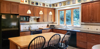 Spacious kitchen with butcher block island. Cabinets are black walnut from the property and Albemarle County soapstone countertops.