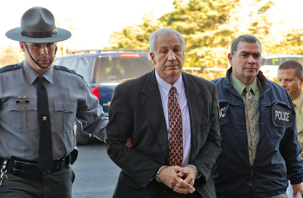 Former Penn State football defensive coordinator Jerry Sandusky, second from left, arrives at the office of Centre County District Justice Leslie A. Dutchcot while being escorted by Pennsylvania State Police and Attorney General's Office officials in State College, Pa. on Saturday, Nov. 5, 2011. Sandusky was arraigned following a grand jury investigation related to numerous child sex abuse charges. Photo by Andy Colwell for The Patriot-News