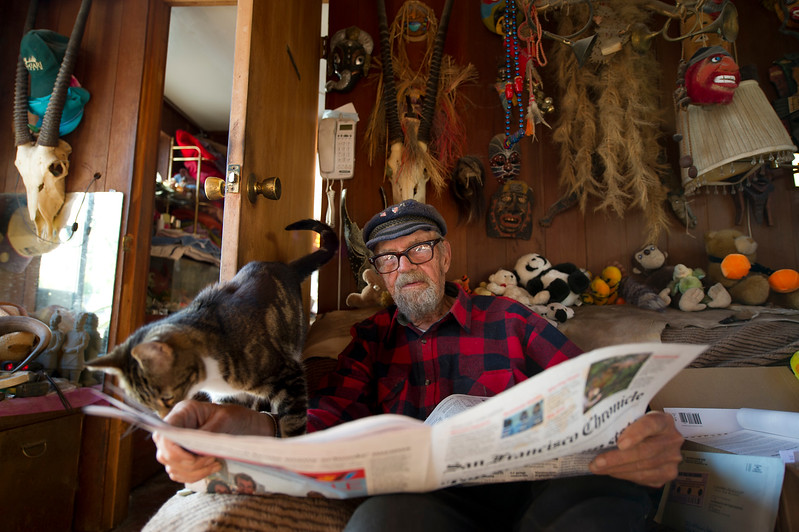 "Ashley the cat vies for Srnka's attention as he reads the newspaper in his houseboat, ""The Hunter,"" on Wednesday, June 6, 2012. He's owned numerous boats for fishing and for living since moving to Mission Creek Harbor in 1972, and he now pays his most of his mooring fees by renting out the three-story houseboat's top level"