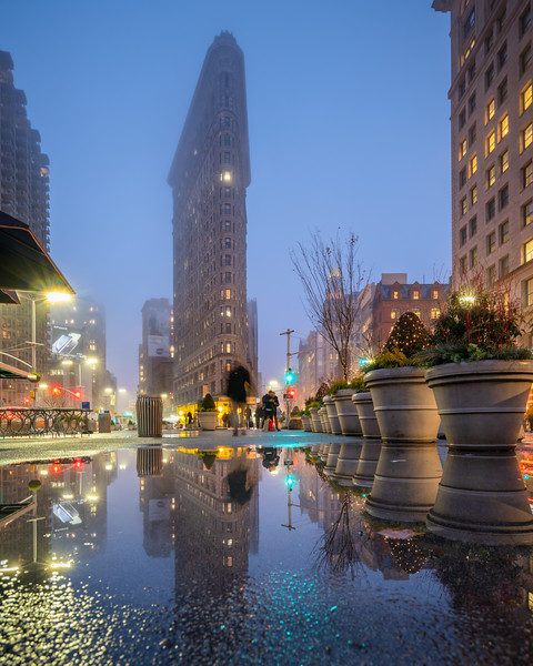 Flatiron Building and its reflection in a puddle after the rain.