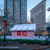 Gingerbread House in Madison Square Park with the Flatiron Building at sunset.