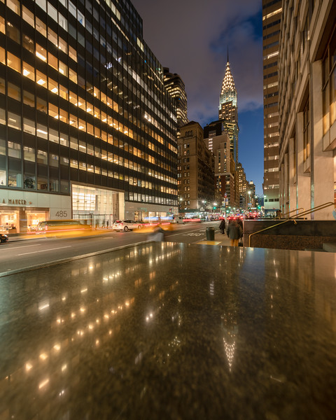 Chrysler Building, a speeding taxi, and Chrysler's reflection in a granite ledge.