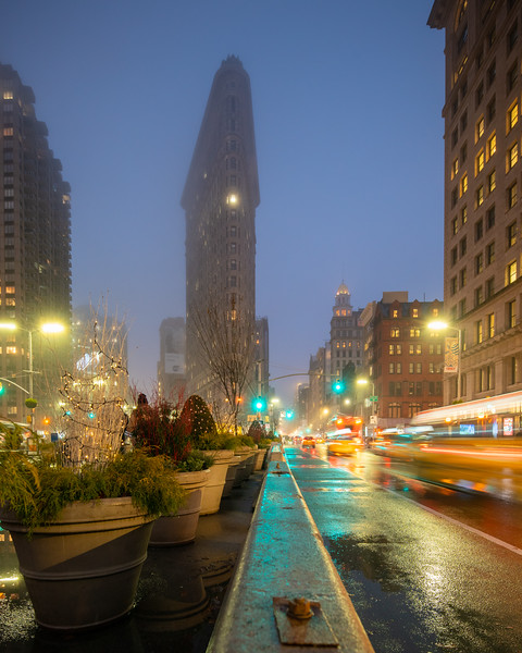 Flatiron Building, speeding taxi and a traffic barrier after the rain.
