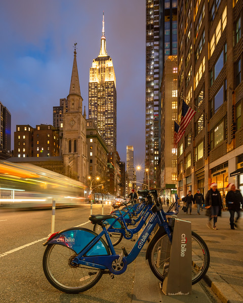 Empire State Building, Marble Collegiate Church, Citibikes, speeding bus, and two people with Santa hats.