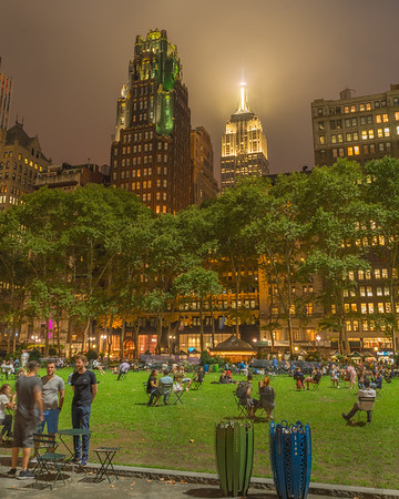 Empire State Building and Bryant Park Hotel with Bryant Park in the foreground, blue hour in the fog.