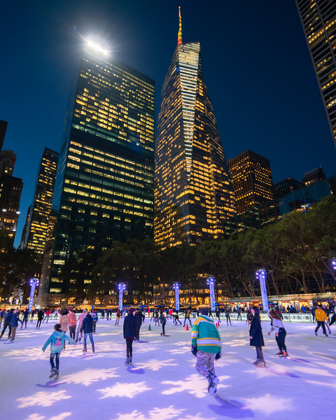 Skaters in Bryant Park with the Bank of America Tower in the background during the blur hour.