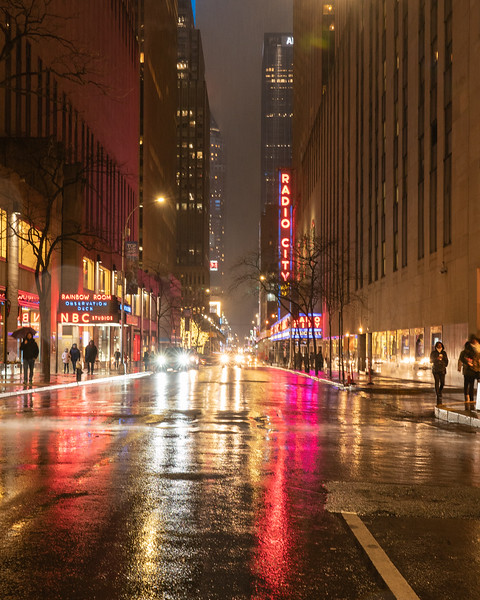 Radio City Music Hall and NBC Studios entrance on 50th Street in the rain during the blue hour.