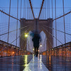 Walking alone with an umbrella in the rain on the Brooklyn Bridge.