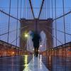 Walking alone with an umbrella in the rain on the Brooklyn Bridge.