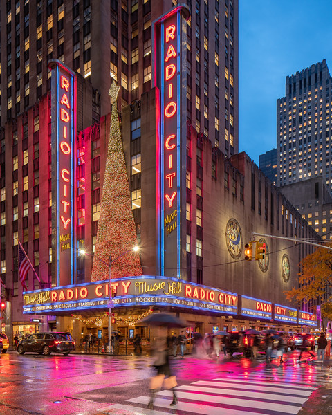 Radio City Music Hall in the rain during the holidays with a woman crossing the street.