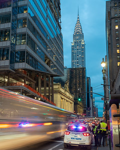 Chrysler Building with a speeding bus and NYPD traffic cop meeting to the right.
