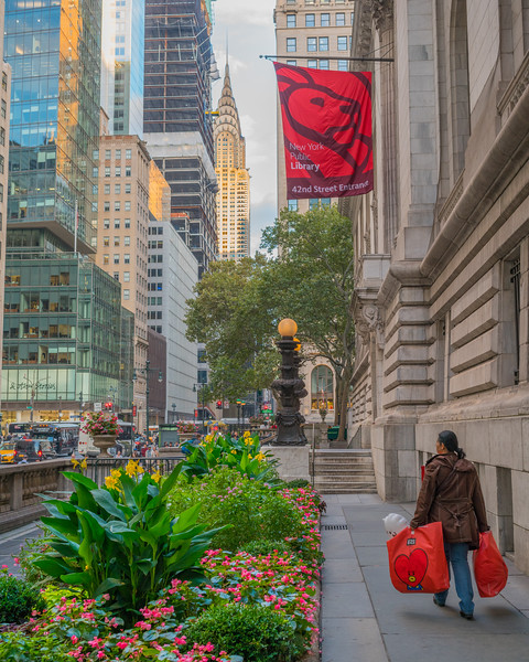 Woman with bags walking next to New York Public Library.