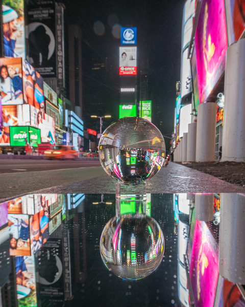 View of Times Square through a Lensball crystal ball reflected in a mirror, with snow flurries.  Orange, purple, green and blue colors.