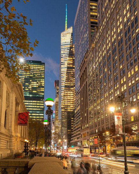 Bank of America Tower and NY Subway green & white sign posts in the foreground, during the blue hour.