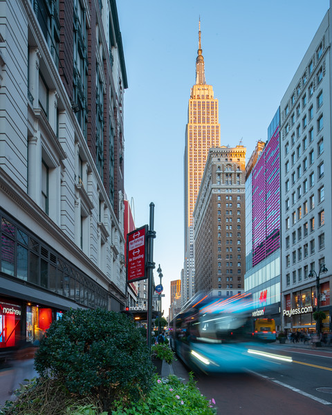 Empire State Building with a passing bus during the golden hour.