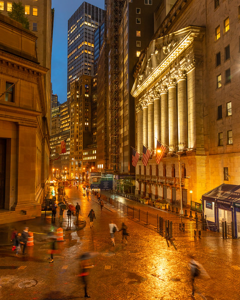 New York Stock Exchange and Wall Street in the rain during the blue hour.