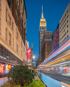 Empire State Building and a speeding bus in blue and yellow.
