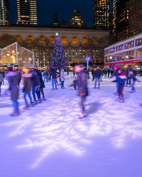 Ice skating in Bryant Park with the Christmas Tree and New York Public Library in the distance.