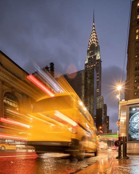 Chrysler Building, Grand Central Terminal, and a speeding taxi in the rain.
