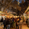 Bryant Park Winter Village stores and the Empire State Building in the evening.